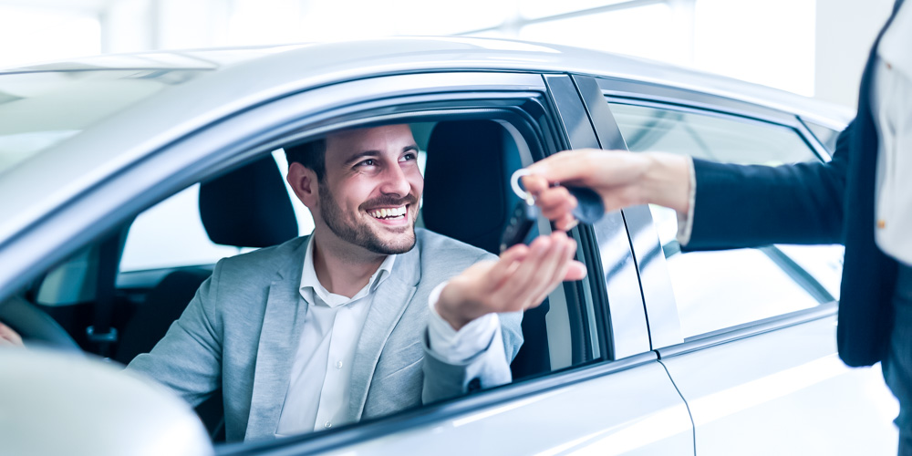 Person giving keys to man in a car